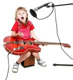 Girl in audio studio. Little girl sing to studio microphone and play with red electric guitar Royalty Free Stock Images