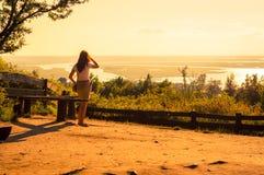 Girl aufpassende Seen im Vordergrund während des erstaunlichen Sonnenuntergangs Stockbilder