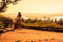 Girl aufpassende Seen im Vordergrund während des erstaunlichen Sonnenuntergangs Stockfotos