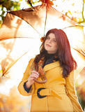 Girl in autumn. Beautiful girl with umbrella in bright sunlight Royalty Free Stock Photography