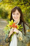 Girl with autumn bouquet in park Stock Photography