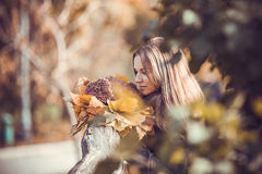 Girl with autumn bouquet in park Stock Photos
