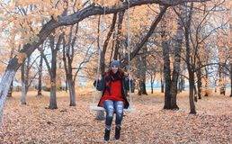Girl in autumn city park in leaf fall. Young beautiful mother wi Stock Images