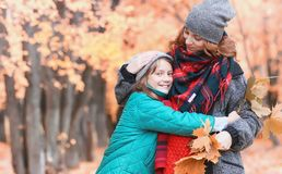 Girl in autumn city park in leaf fall. Young beautiful mother wi Stock Photo