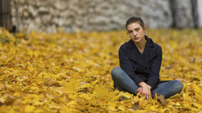 Girl in autumn city Park sits on the fallen leaves. Young girl in autumn city Park sits on the fallen leaves royalty free stock photos