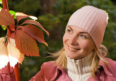 Girl in autumn clothes. Beautiful girl in autumn clothing with a bunch of colorful leaves Stock Image