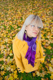 Girl in autumn colours. Colourful girl standing on yellow autumn leafes Stock Photos
