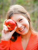 Girl in autumn forest. The girl smyle with an apple royalty free stock images