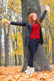 Girl in autumn forest keep leaves in the hands, stand near big tree Stock Photo
