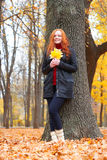 Girl in autumn forest keep leaves in the hands, stand near big tree Royalty Free Stock Photo