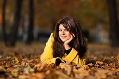 Girl in autumn. Happy beautiful girl in autumn with yellow leaves Royalty Free Stock Image