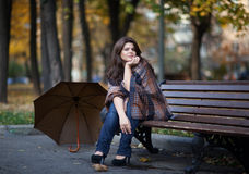 Girl in autumn. Girl with her umbrella on the bench Stock Image