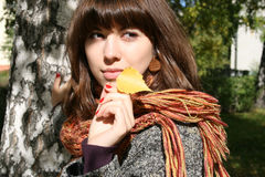 The girl with an autumn leaf. Royalty Free Stock Photo