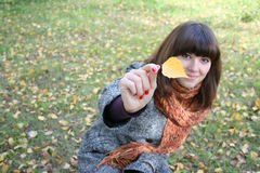 The girl with an autumn leaf. Royalty Free Stock Images