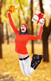 Girl with autumn leaf jump outdoor. Royalty Free Stock Photo