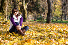 Girl in autumn leaves. Young woman posing in autumn leaves stock photography