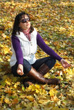 Girl in autumn leaves Stock Image