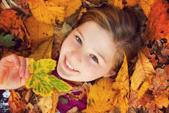 Girl on autumn leaves Royalty Free Stock Images