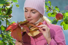Girl with autumn leaves. Beautiful girl with autumn leaves near the apple tree and blue foggy background behind her Stock Photography