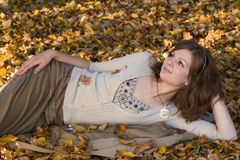 Girl on autumn leaves. Girl lying on autumn leaves Royalty Free Stock Photography