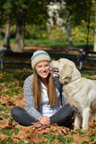 Girl in autumn leaves and dog Royalty Free Stock Photo