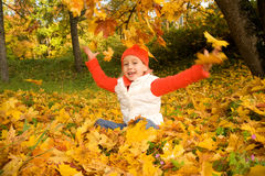 Girl with autumn leaves outdoors Stock Image