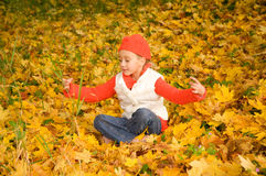 Girl with autumn leaves outdoors Stock Images