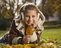 Girl with autumn leaves in park Royalty Free Stock Photos