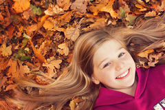 Girl on autumn leaves smiling Royalty Free Stock Photo