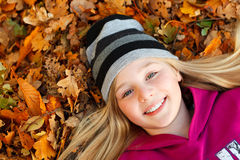 Girl on autumn leaves smiling Stock Photo