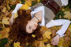Girl on autumn maple leaves. Girl lying in maple leaves on sunset time Stock Images