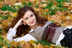 Girl on autumn maple leaves. Laughing Girl lying in maple leaves on sunset time Royalty Free Stock Images