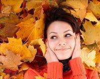 Girl in autumn orange hat on foliage. Royalty Free Stock Images