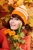 Girl in autumn orange hat on leaf group, flower. Royalty Free Stock Photography