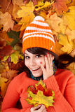 Girl in autumn orange hat on leaves. Royalty Free Stock Image