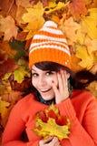 Girl in autumn orange hat on leaves. Girl in autumn orange hat on leaf group. Outdoor royalty free stock image