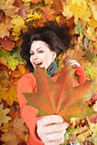 Girl in autumn orange leaves. Outdoor royalty free stock photo