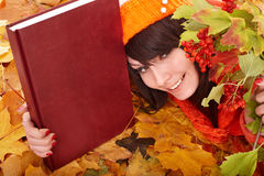 Girl in autumn orange leaves with book. Outdoor stock photo