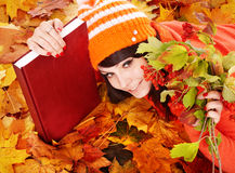 Girl in autumn orange leaves with book. Royalty Free Stock Images