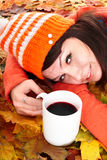 Girl in autumn orange leaves with cup coffe. Outdoor royalty free stock photography