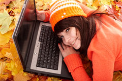 Girl in autumn orange leaves with laptop. Fall sale. Outdoor stock images