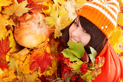 Girl in autumn orange leaves with pumpkin. Young woman in autumn orange leaves with pumpkin. Outdoor royalty free stock images