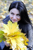 Girl in autumn park. Young beautiful girl in autumn park with yellow leaves in her hands Stock Images