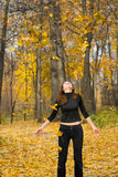 Girl in autumn park. The young girl in autumn park during a leaf fall Royalty Free Stock Image