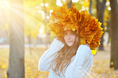 Girl in autumn park, in autumn sunshine and a wreath of leaves.  stock photos