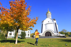Girl in Autumn park and church Stock Photography