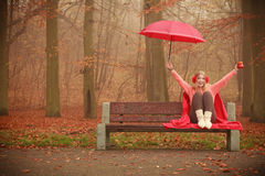 Girl in autumn park enjoying hot drink. Happiness carefree and fall concept. Joyful woman relaxing in autumn park on bench under umbrella enjoying hot drink Royalty Free Stock Image
