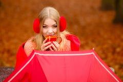 Girl in autumn park enjoying hot drink Stock Photo