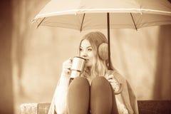 Girl in autumn park enjoying hot drink Royalty Free Stock Photos