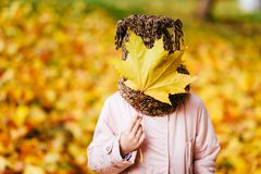 Girl in the autumn Park and found a maple leaf and holds it in t stock image
